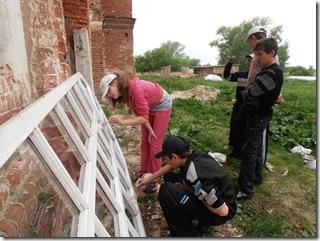 Дети помогают красить рамы для храма