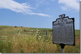 McDowell's Grave marker with family cemetery in background