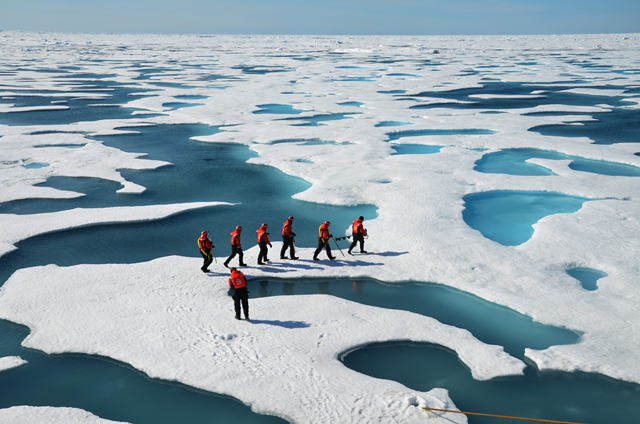 Sea ice researchers, surrounded by Arctic melt ponds, set out to check the thickness of an ice floe. Photo: Don Perovich