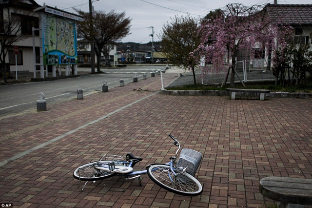 A fallen bicycle lies on a Futaba pavement, abandoned after meltdowns at the Fukushima nuclear plant. AP