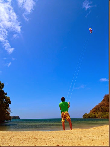 flying a kite in a remote tropical cove