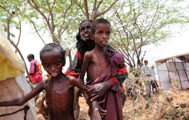 An internally displaced woman attends to her malnourished children outside their makeshift shelter at a temporary camp in Hodan district of Somalia's capital Mogadishu, 26 August 2011. FEISAL OMAR / REUTERS