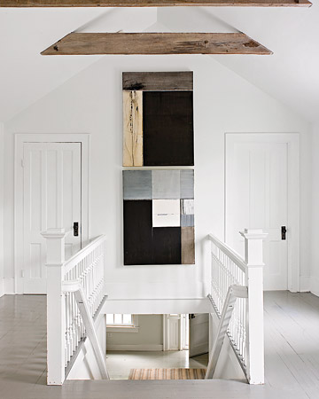 This stark white landing is punctuated by abstract art, completing the pared-down look.