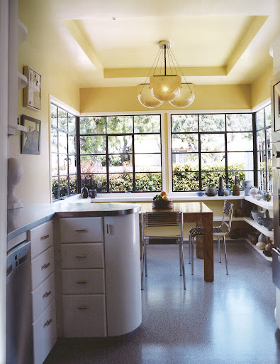 The kitchen in Robert Wilson and David Serrano's Los Angeles home features a Sergio Asti fiberglass light fixture from the 1960s above Paul Evan's burl Parsons table and chairs by Rene Herbst. (Dealer's Choice, Architecture/Interiors Press, Inc.)