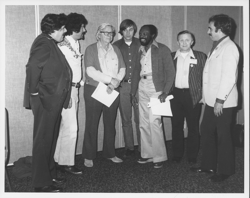 Gay leaders attend the California Democratic Council Convention. The people are (from left) Reverend Ray Broshears, Howard Fox, Morris Kight, Gerry Parker, Willie Brown, Elmer Wilhelm, and unidentified. 1975.