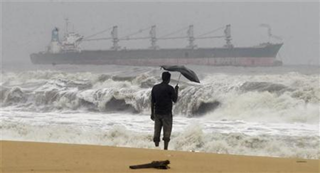 A man holding an umbrella watches large waves on the Marina beach as a cargo ship passes after Cyclone Thane hit the southern Indian state of Tamil Nadu, 30 December 2011. Reuters / Babu