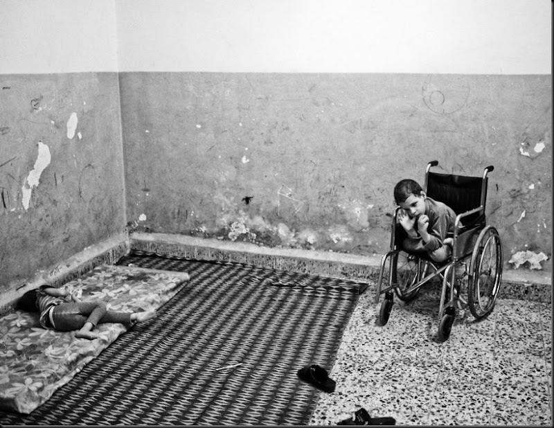 Aziz, 8, (right) and his sister Aisha (left), both suffering from cerebral palsy, inside their family's one-room house in East Amman, an area where a large number of Syrian refugees have settled. (Moises Saman/Magnum Photos for Save the Children)