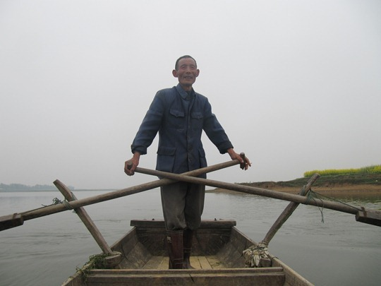 A Chinese man patrolling a lake for illegal fishing