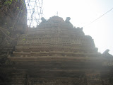 View of the roof of this mukha-mandapa. The Sun was not in right direction so the photo is not very clear. This roof is a recent addition to the temple. Various dancers' images are sculpted on the horizontal strip. In the central panel is shown a goddess under a makara-torana sitting over her mount.