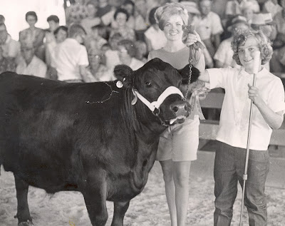 Janice (Schneider) Carr remembers how 4-H was always a family event travelling to the State Fair and Cattle Congress.  She showed beef during her 10 years in 4-H for the Clover Cloverettes 4-H club. Here Queen Abbie (Timmins) Parmele awards Carr during a beef show in 1967.  She said one of her favorite 4-H highlights were the trips to Washington D.C.    Carr's three children were a part of  Washington County 4-H and now she serves on the Youth Committee.  Photo Courtesy:  Washington County Extension.