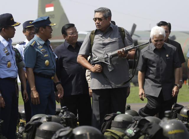Indonesian President Susilo Bambang Yudhoyono, center, holds an assault rifle as he inspects the task force that will be deployed to help battling forest fires on Sumatra island, at Halim Perdanakusumah airbase in Jakarta, Indonesia, Tuesday, 25 June 2013. Yudhoyono apologized Monday to Singapore and Malaysia for record-setting pollution caused by forest fires on Sumatra island that have sent massive plumes of smog across the sea to the neighboring countries. Photo: Dita Alangkara / Associated Press