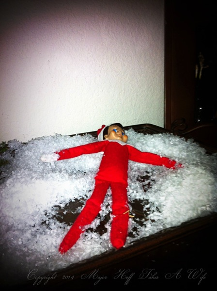 Elf on the shelf playing in snow