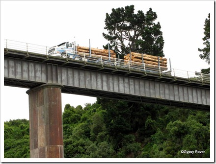 Logging truck slowly passing over the Waimakariri Gorge road bridge.