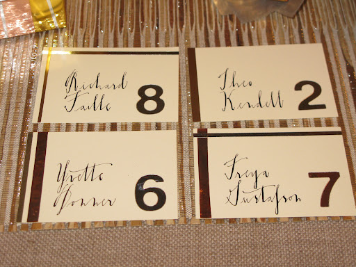 Escort Cards from the metallic story!  Vinyl numbers from Duall​. Crane & Co. escort cards. Nasco metallic Mylar craft tape.  Art­Emboss copper foil tape from Robert's​ Crafts. Canford card stock in metallic silver from NY Central Art Supply.  Caligraphy by Diva Pyari of Linea Carta.