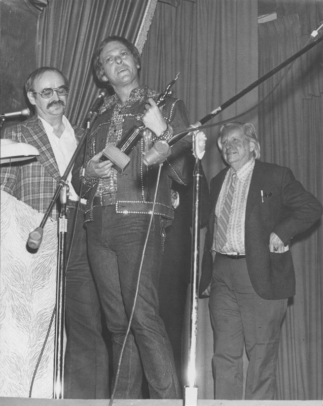 Lee Glaze accepts an award from Jim Kepner (glasses) and Morris Kight at the SPREE (The Society of Pat Rocco Enlightened Enthusiasts) Awards. 1973.