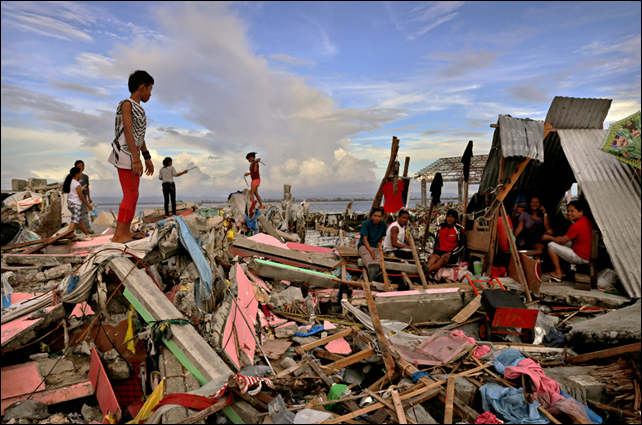 Residents gather amongst the devastation in the aftermath of Typhoon Haiyan on 13 November 2013 in Tacloban, Leyte, Philippines. Typhoon Haiyan, packing maximum sustained winds of 195 mph (315 kph), slammed into the southern Philippines and left a trail of destruction in multiple provinces, forcing hundreds of thousands to evacuate and making travel by air and land to hard-hit provinces difficult. Photo: Kevin Frayer / Getty Images
