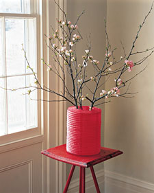 Brighten up a simple floral arrangement by using a colorful paper lantern as a sleeve for a vase. (marthastewart.com)