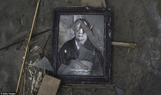 Treasures left behind in Minamisoma, Japan after the Fukushima nuclear meltdowns: An old black and white photograph still in its shattered, blackened frame, is left behind in the rubble. Getty Images / dailymail.co.uk