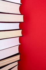 Stack of thick encyclopedias against red background
