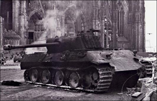 """Сгоревший немецкий танк PzKpfw  """"Пантера """" на фоне Кельнского собора.  Фото сделано через несколько часов после боя."""