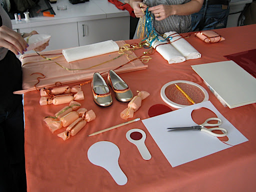 One of our work stations. The coral, red, and peach work station, apparently. That's me and our intern Stephanie working on the ring pillows.