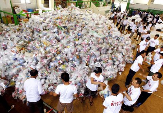 Police and volunteers form a human chain to load plastic packed care packages of basic foods and sanitary items into waiting trucks for transport to flood victims in Bangkok, Thailand, 29 October 2011. EPA