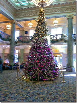 The bottom half of the Christmas tree is decorated with purple ornaments and the top half, gold.