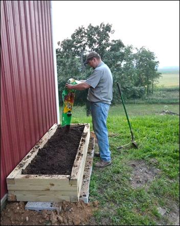 add potting soil to herb garden