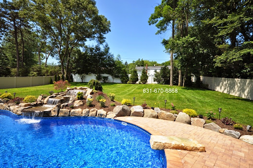 Pool Waterfall- in-ground vinyl swimming pool -Contractor - Long island NY     http://deckandpationaturalstones.com/swimming-pool-Gunite-Vinyl-Fiberglass-Builders-long-island-ny.html  Within this photo we percieve a lovely natural waterfall having an in ground vinyl swimming pool area in Lake Ronkonkoma, New York (11779). Along with this being water fall beautiful however it an excellent entertainment piece for all of your friends and relations have fun with. Across the pool we view various kinds of landscaping that reveal the shades inside the paving stones that comprise the swimming pool patio. Off the pool we come across a driving rock which will keep the colour scheme in the patio going and adds some move fun towards pool. Out lining the entire backyard we view an excellent Azek white PVC fencing, this provides this backyard a much cleaner cut look. The mixture of most these components results in a backyard all will love mainly in the warm summer seasonn.http://deckandpationaturals