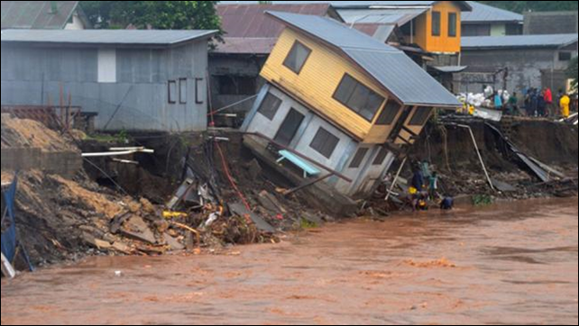 A building teeters on the edge of the Matanikau river after record flooding in Honiara, Solomon Islands, 3 April 2014. Photo: Solomon Star / AP