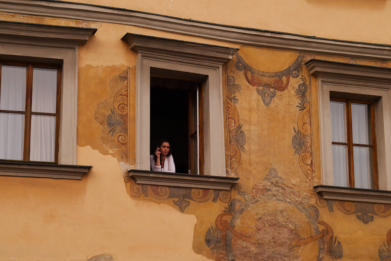A local women looks bored to the stream of tourists which cross the Charles bridge, Prague, Czech Republic.