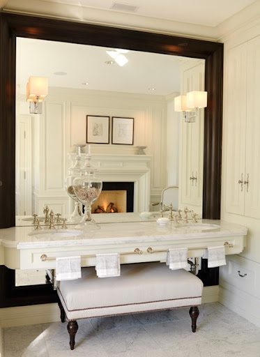 The oversized framed mirror and tucked ottoman add great interested to this bathroom -- the fire place doesn't hurt either. (houseandhome.com)