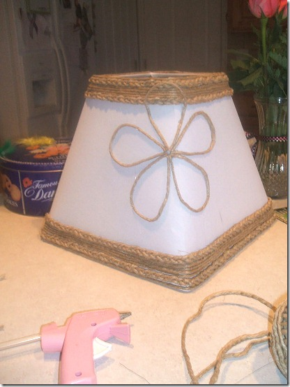White lamp shade trimmed with jute and embellished with jute flower