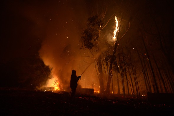 A firefighter battles a fire in New South Wales, 9 January 2013. PA