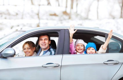 Happy family driving in  the car surrounded by snow.