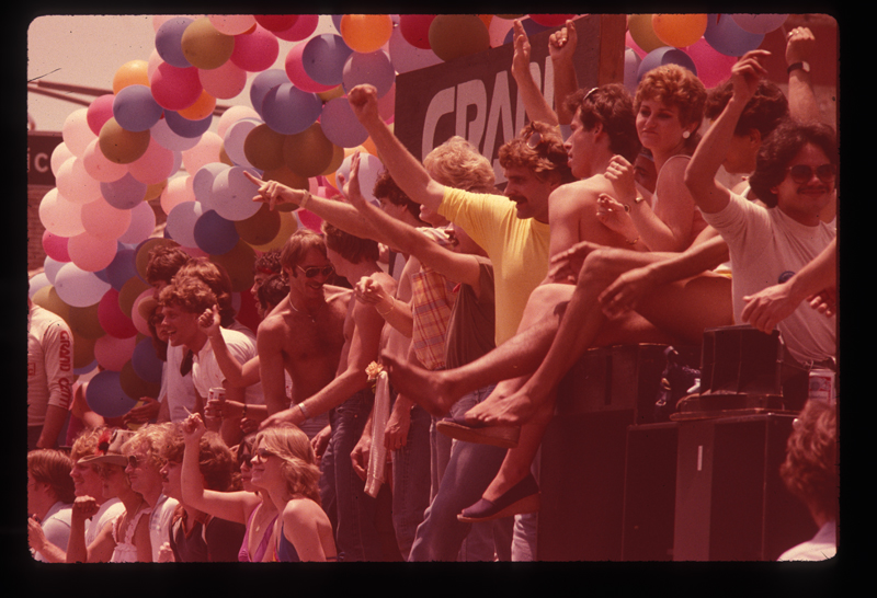 Crowd celebrating along the route of the Los Angeles Christopher Street West pride parade. 1982.