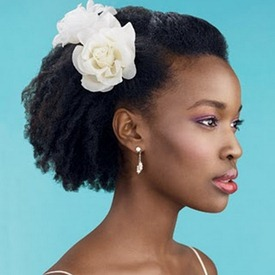 Easy to do pinned natural hair style with flower accessory