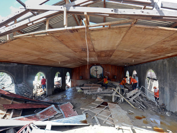 Workers clear debris inside a church swept in by flash floods caused by Typhoon Bopha, in the village of Andap in the town of New Bataan in Compostela Valley province, the Philippines, on 8 December 2012. Ted Aljibe / AFP / Getty Images
