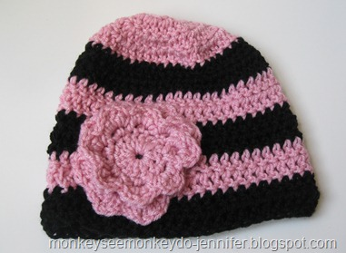 pink and black striped hat with flower