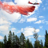 One of the USFS's famous slurry bombers drops retardant on a forest fire.