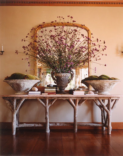 Over-sized moss arrangements anchor a whimsical wooden console, putting the focus on a truly fantastic center arrangement.