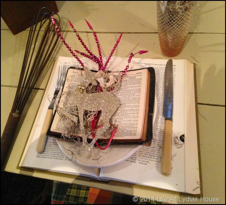 Round top table with books, Bibles, ornaments and whisks close up via Life At Lydias House
