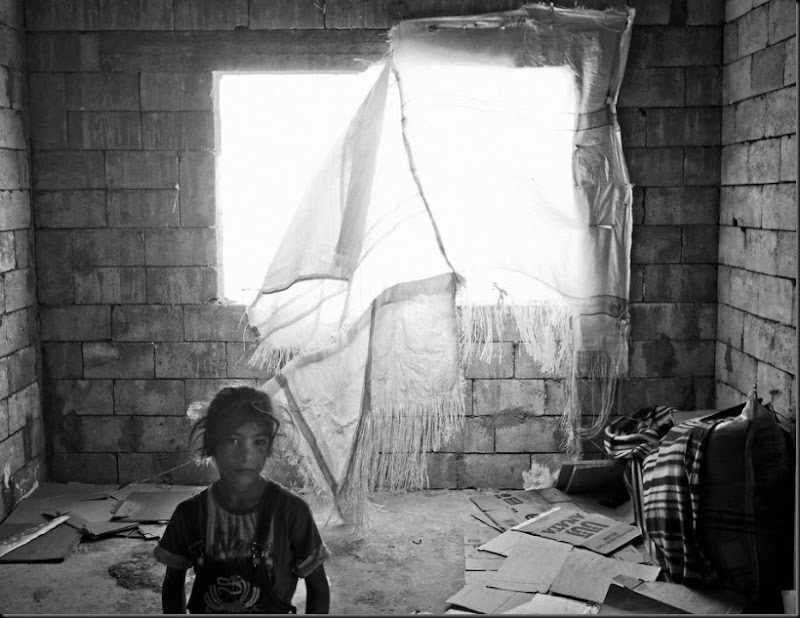 A young Syrian refugee inside her family's temporary home in an unfinished building. (Moises Saman/Magnum Photos for Save the Children)