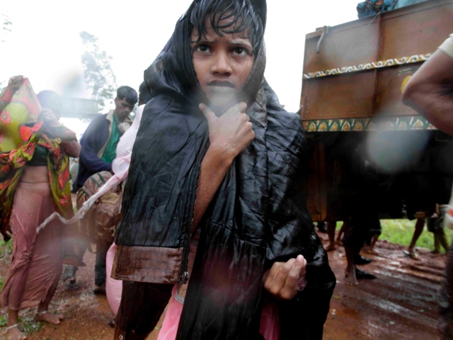 A young Indian boy reaches a relief camp after being evacuated as it rains near Berhampur, India, 12 October 2013. Hundreds of thousands of people living along India's eastern coastline were taking shelter Saturday as Cyclone Phailin hit landfall. Photo: Bikas Das / The Associated Press