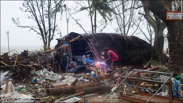 This handout photo taken and received on 14 March 2015 by UNICEF Pacific shows residents looking through storm damage caused by Cyclone Pam, in the Vanuatu capital of Port Vila. Photo: UNICEF Pacific