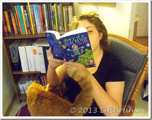 TailorBear reads Diary of a Real Payne with cat on her lap.