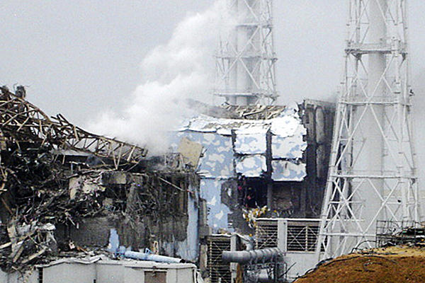 The damaged No. 4 unit of the Fukushima Daiichi nuclear complex in Okumamachi, Japan, 15 March 2011. White smoke billows from the No. 3 unit. Tokyo Electric Power Co. via Kyodo News / AP