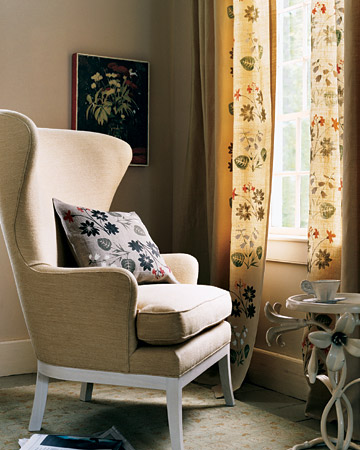 Two handmade floral stencils, arranged agreeably askew, decorate the inner edges of curtains, framing the window.