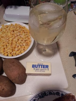 potatoes, corn, butter and glass of wine