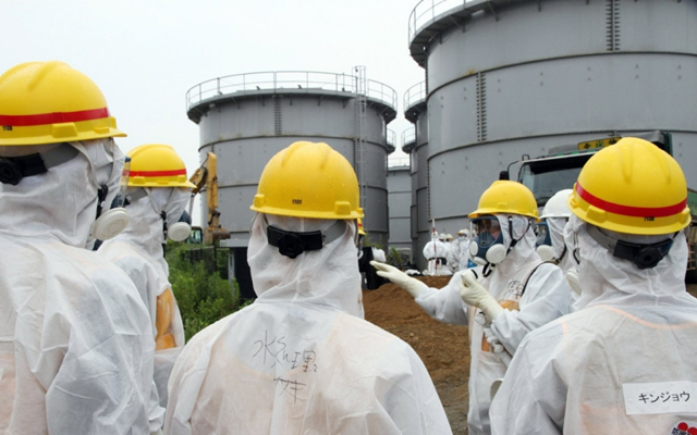 Workers at leaking water tanks at the Fukushima nuclear plant. Photo: Japan Pool / AFP / Getty Images